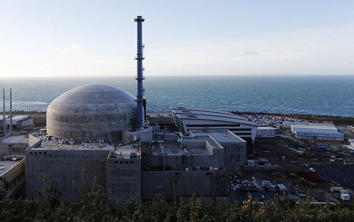 Лучи августовского солнца едва пробиваются сквозь густой туман, окутывающий АЭС «Фламанвиль», расположенную в департаменте Манш. С вершины прибрежной скалы с трудом можно различить очертания бетонных ограждений, которыми окружены два действующих реактора и энергоблок модели EPR. Похоже, что рядом с ними никого нет. Огромная парковка на несколько сотен мест пуста.