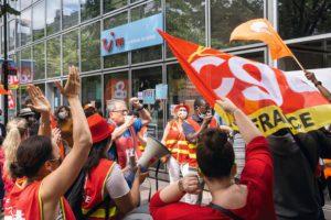 После того как руководство TUI объявило о намерении сократить две трети рабочих мест во Франции, сотрудники этой туристической компании собрались у дверей офиса. Понимая, что их ждёт потеря работы, эти люди борются за достойные условия увольнения.